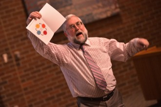 David Reinhold holds up a booklet during a presentation.