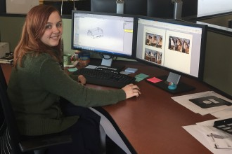Emily Gruss sitting at a desk in front of two computer displays.