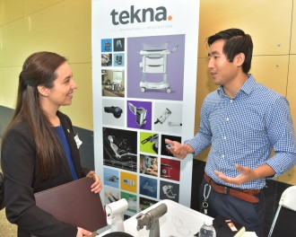 A student learns about Tekna from a company rep participating in the Engineering Expo.