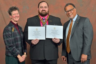Joshua White displays his two Presidential Scholar certificates flanked by the presidents of WMU and its Faculty Senate.