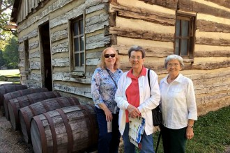 Photo of three women standing in front of the log cabin featured on the trip.