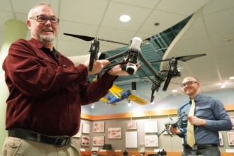 Emerson and Mathews holding examples of the drones at their disposal.