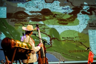 Ensemble member on stage discussing a projection of a map.