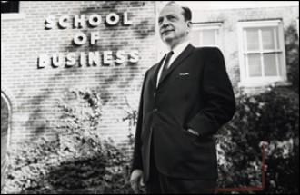 Arnold Schneider in front of the School of Business sign