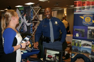 Student talking to a MI State Police Officer at the career fair