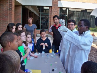Elementary school students watching an experiment