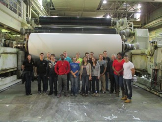 Students and faculty standing in front of huge machinery
