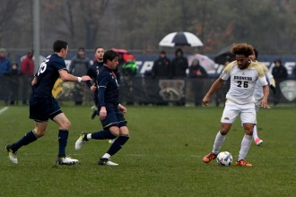 WMU men's soccer player No. 26 Jay McIntosh kicks the ball as Akron players approach on field.