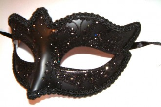 Photo of a black, decorative, theatrical eyemask with sequins resting on a white backdrop.