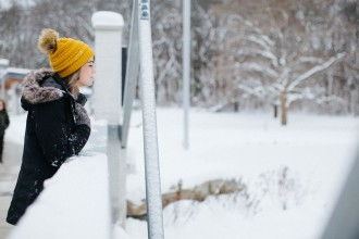 A female WMU student wearing a gold hat is standing on the bridge overlooking a snowy Goldsworth Valley Pond.