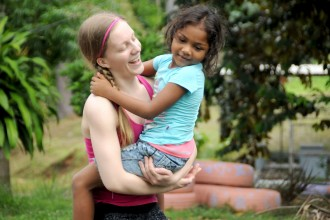 Photo of Kelci Winchell posing with a child from the orphanage.