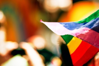 Photo of a rainbow flag at a gathering.