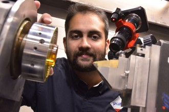 Photo of Dr. Deepak Ravindra looking inside a laser-assisted machining setup.