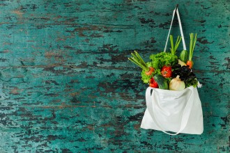 Photo of a fresh vegetables hanging in a natural cotton recyclable shopping bag.