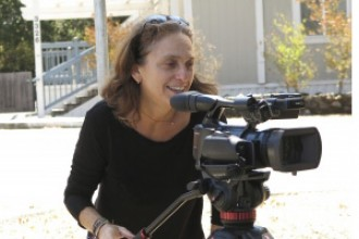 Photo of Lisa Klein, documentary director, standing behind a camera on a tripod.