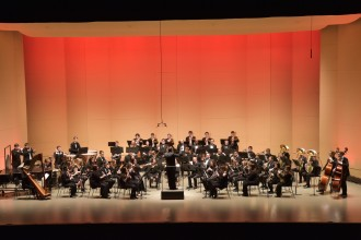 University Symphonic Band on a stage with members playing their instruments.
