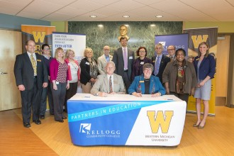 Group of administrators from Kellogg Community College and Western Michigan University pose at an event where the transfer agreement was signed. KCC President Mark O'Connell and WMU Interim Provost Susan Stapleton sit at a table in the front signing papers.