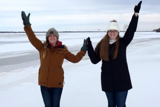 Two WMU students, Kayla Combs and Kayla Poole, pose on an iced-over lake, forming a W with their outstretched arms.