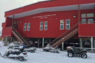 Snowmobiles sit parked outside a red school building, Kaltag Elementary and Secondary School.