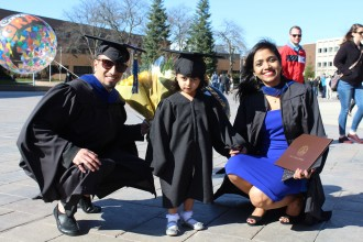 Two graduating WMU students pose with a young child outside of Miller Auditorium after their commencement ceremony.