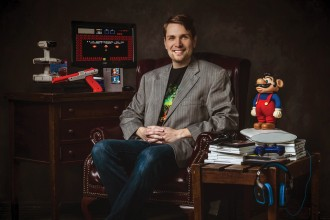 WMU's Dr. Whitney DeCamp sits in an office surrounded by video game paraphernalia.