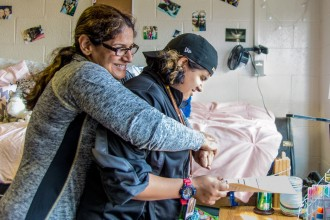 A mom embraces her child, a student at WMU, as they hang out together in the dorms.