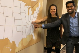 Two WMed students point to the state of Kentucky on a U.S. map during their Match Day event.