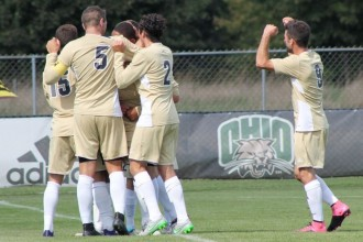 Four Bronco men's soccer players are huddled in a circle on a soccer field and another player runs toward them.