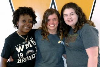 Three WMU student employees pose in front of a gold W.