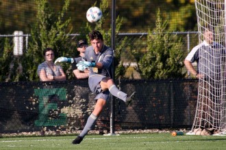 Photo of Bronco men's soccer player Drew Shepherd on a field kicking a ball from the goal.