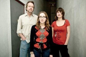 Tom Rainey Trio, consisting of Tom Rainey, Ingrid Laubrock and Mary Halverson, stand in front of a gray wall.