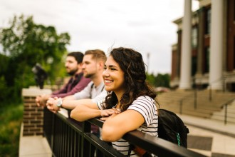 Photo of three WMU students leaning over a railing atop the hill near East Hall.