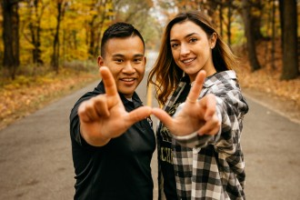 Two WMU students stand on a country road with fall leaves in the background. They make a W with their hands.