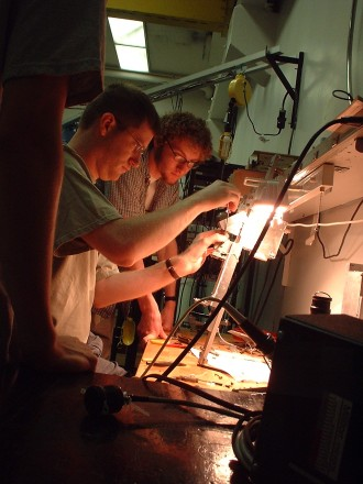 A WMU physics postdoc and graduate student building an instrument for their experiment.