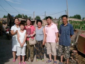 Photo of Dr. Ann Veeck with a family in China.