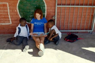 WMU student reading to African children.