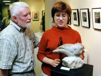 a photo of a professor and a visually impaired student examining what a sculpture. The student has her hand on the sculpture and is feeling the relief carving of the piece of art. It's difficult to tell what the sculpture is from the angle the photo is taken, it may be a small owl, or something entirely abstract.