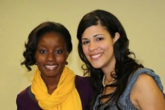A photo of two students smiling and looking at the camera. The woman on the left is wearing a brown top with a gold scarf, and the woman on the right is wearing a blue top.