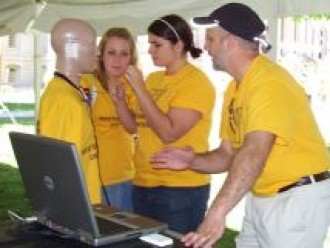 a photo of three students working with a manequin that has a sensor attached to it's head. The students and the manequin are all wearing matching yellow shirts.