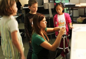 a photo of a student teacher showing elementary students how to use a digital camera in a classroom. The camera is on a tripod which is set at table height to capture an image of a paper that's been placed on the table.
