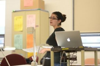 a photo of a teacher at the front of a classroom speaking. She has a laptop that is open for a presentation, but at the moment is holding a piece of paper and speaking to the class about it.