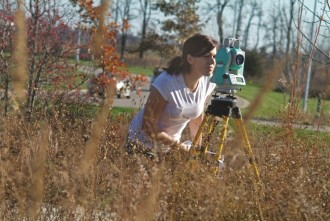 A photo of a student in the field standing behind a piece of equipment on a tripod. She is looking through an eyepiece of what may be a camera or a surveyor's tool.