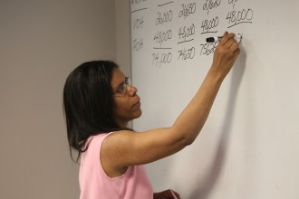 A photo of a woman writing a sequence of large numbers on the white board at the front of a classroom.