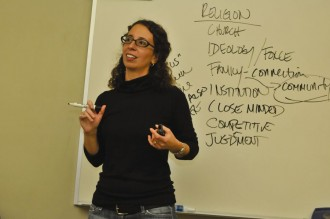 a photo of a professor at the front of a whiteboard in a classroom with a marker in one hand and an eraser in the other. She is explaining the list of terms that she has written on the board.