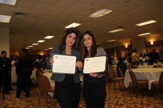 this photo shows two international students at an awards ceremony. Both women are holding up certificates of recognition for their out standing work as students at W M U .