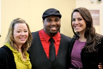 This photo has three smiling and friendly looking students standing side-by-side. All three are wearing dark jackets with colorful shirts. The blonde woman on the left is wearing a mustard yellow blouse, the man is wearing a red dress shirt with dark tie and a matching cap. The brunette woman on the right is wearing a purple blouse