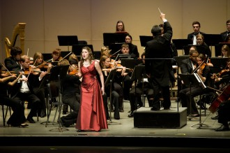 a photo of a woman in a red formal dress singing in front of an orchestra dressed in black at Western Michigan University