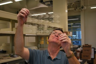 a photo of a man holding up a mostly transparent sheet of plastic with some printing on it. He is holding it up to the light, to see any imperfections in the printing process.