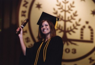 a photo of a student wearing a graduation cap and gown holding her diploma in front of a large wall hanging of the official seal of Western Michigan University