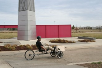 a photo of a man riding a recumbent tricycle past the spire of the Engineering College at Western Michigan University. The tricycle is very long with two small weels in the front and a larger wheel in the rear